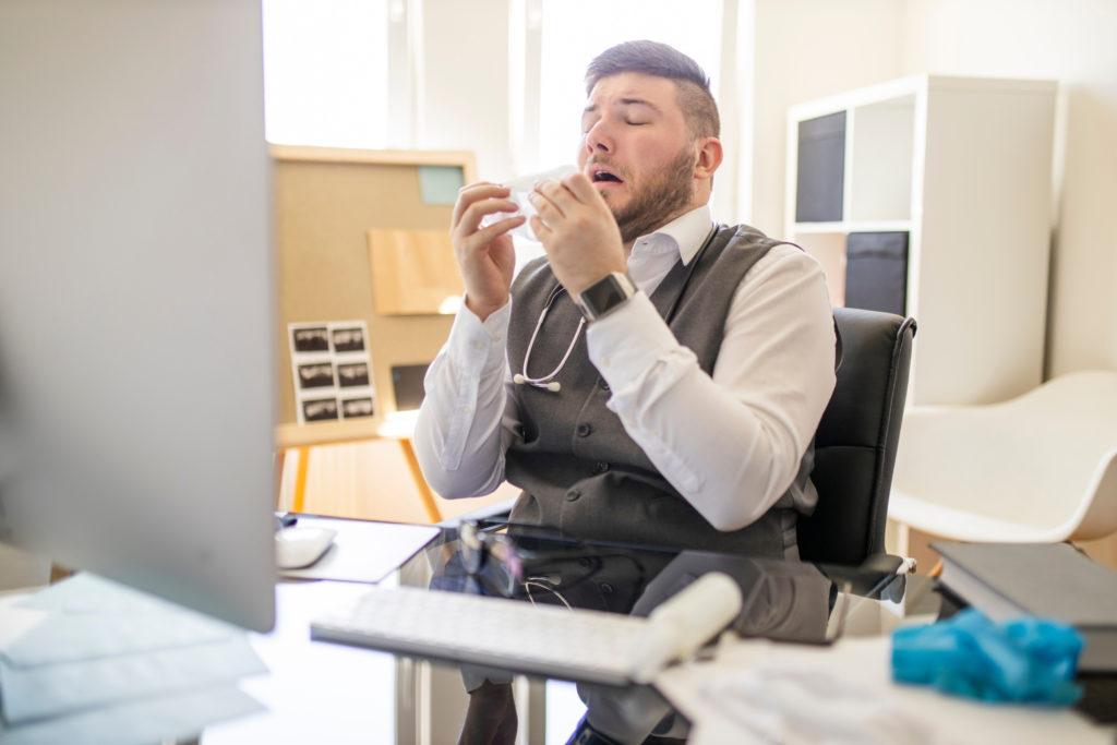 Un médecin éternuant dans un mouchoir qu'il manipule avec ses mains